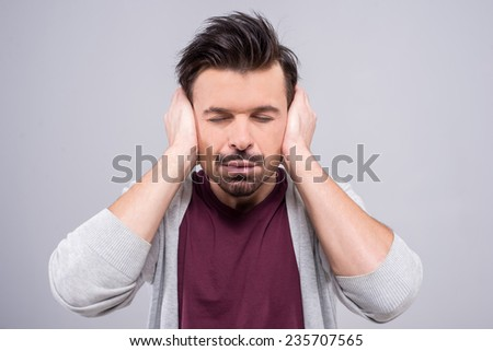 Young man closed his ears because too loud, isolated on a gray background. - stock photo