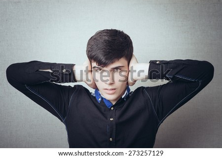 Young man closed his ears with his hands, a gesture not want to hear too loud. On a gray background - stock photo
