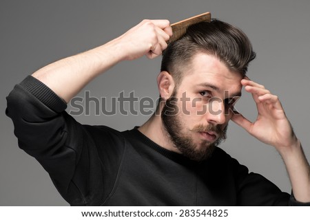 young man comb his hair on gray background - stock photo