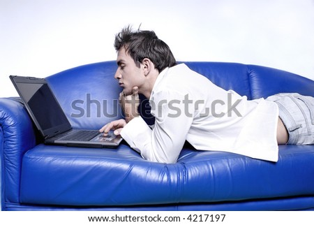 Young man comfortably laying on a sofa using a laptop