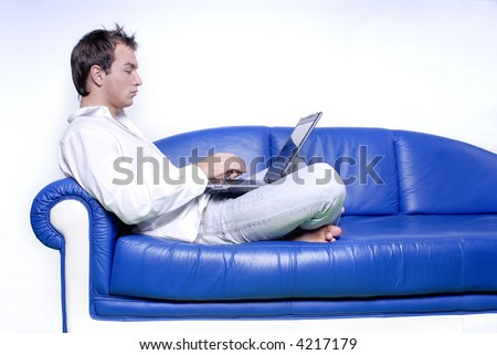 Young man comfortably sitting in a sofa using a laptop
