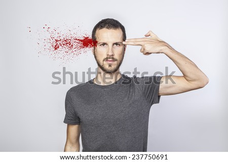 young man committing suicide with finger gun gesture - stock photo