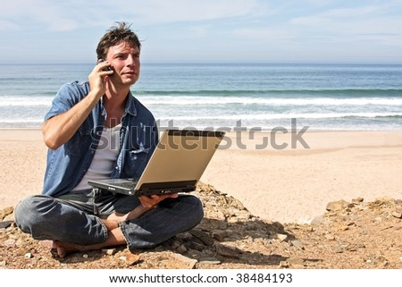 Young man communicating with the world sitting in front of the ocean - stock photo