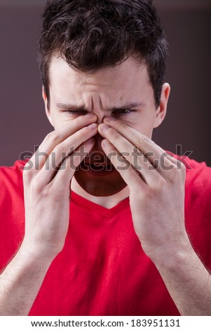 Young man complaining about having sinus pain - stock photo