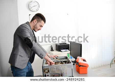 young man computer home repair fixing a computer  - stock photo