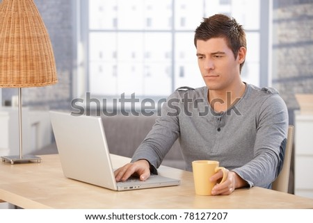 Young man concentrating on laptop computer screen, sitting at desk in living room, holding mug.?