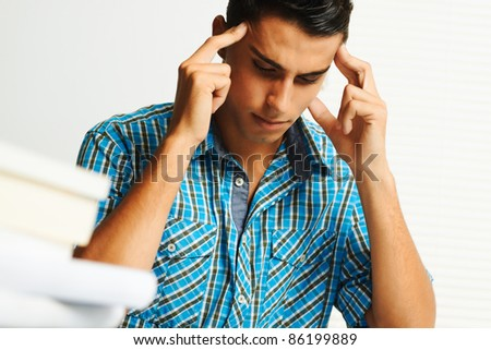 Young man concentrating while studying. - stock photo