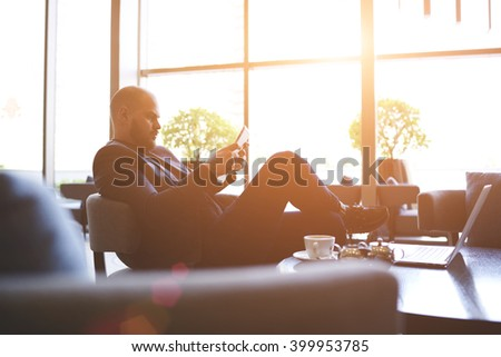 Young man confident entrepreneur is reading financial news via internet on portable touch pad, while is relaxing in cozy cafe. Male proud CEO is using digital tablet, while is waiting partner in bar - stock photo
