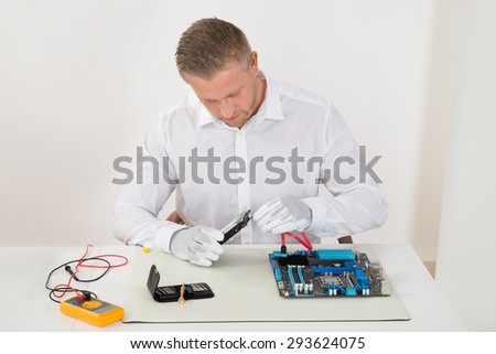 Young Man Connecting Harddisk With The Motherboard At Desk - stock photo