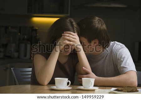 Young man consoling woman at dining table in house - stock photo