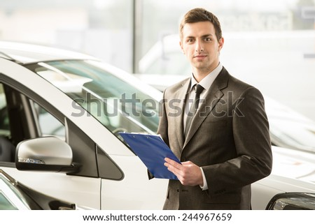 Young man consultant in showroom is standing near car. - stock photo