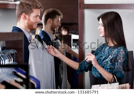 Young man consults with girlfriend while selecting a fashionable shirt - stock photo