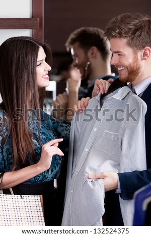 Young man consults with girlfriend while selecting a stylish shirt - stock photo