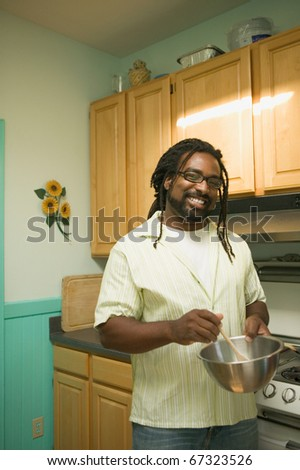 Young man cooking in the kitchen - stock photo