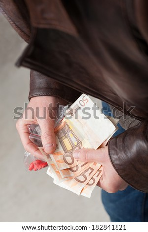 Young man counting earned money from drug selling - stock photo
