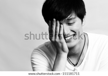 Young man covering his face and laughing