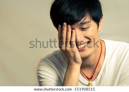 Young man covering his face and smiling, with fashion tone