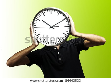 young man covering his face with a clock over green background - stock photo