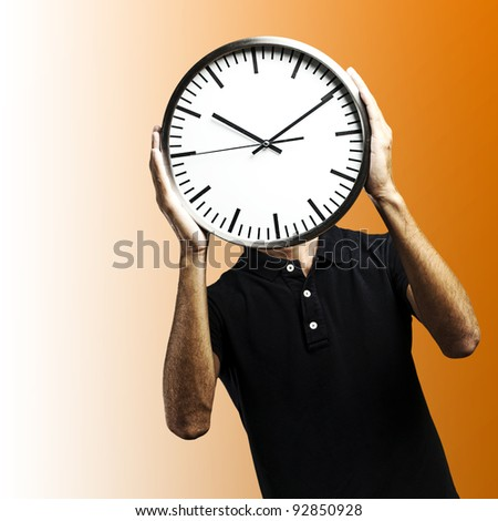 young man covering his face with a clock over orange background