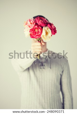 young man covering his face with bouquet of flowers. - stock photo