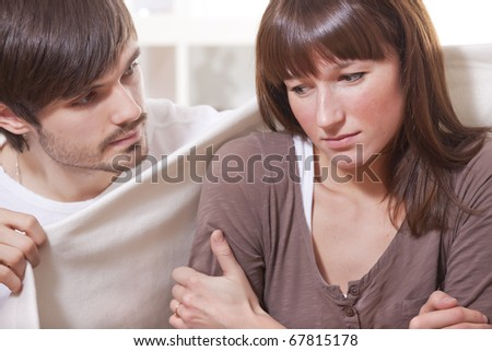 young man covering ill woman with rug at home - stock photo