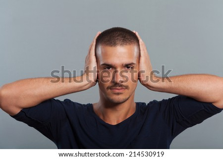 Young man covers ears with hands. - stock photo