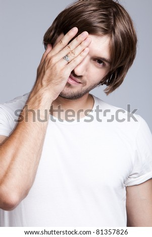 young man covers face with hand, studio shot - stock photo