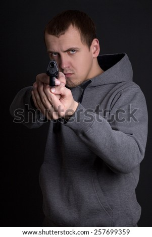 young man criminal aiming with gun over grey background - stock photo