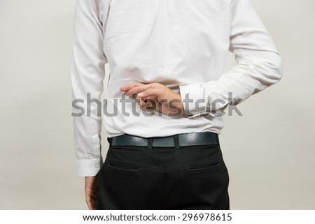 young man crossed his fingers behind his back. - stock photo