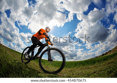 Young man cycling on a rural road through green meadow