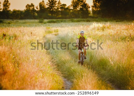 Young man cycling on a rural road through green spring meadow during sunset  - stock photo