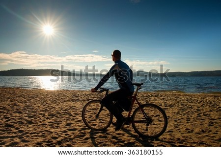 Young man cyclist sit on bike,  blue sky and sunset background on beach. End of season at lake and popular tourist resort..