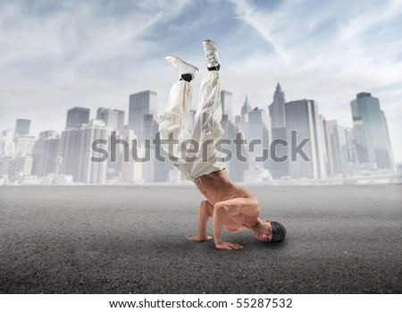 Young man dancing hip-hop with cityscape on the background - stock photo