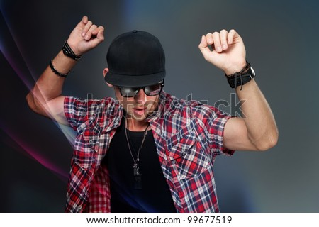 young man dancing in a baseball cap and sunglasses - stock photo