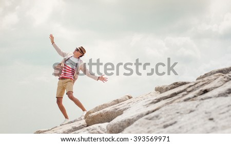 Young  man dancing on rock, feel freedom, blue sky background. - stock photo