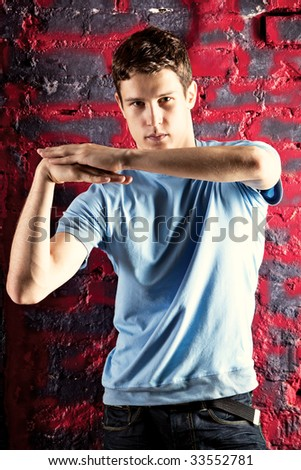 Young man dancing pose. On red stone wall background. - stock photo