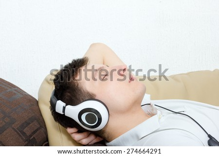 Young man daydreaming listening to music over headset with eyes closed and hand behind his head - stock photo