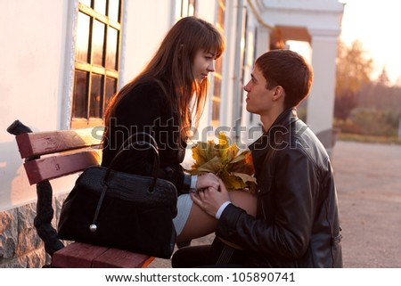 Young man declaration of love for young woman. Couple in love in sunny evening autumn outdoors - stock photo