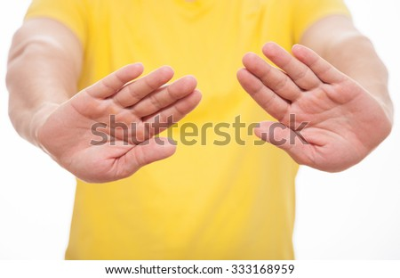 Young man demonstrating prohibiting of a gesture, white background - stock photo