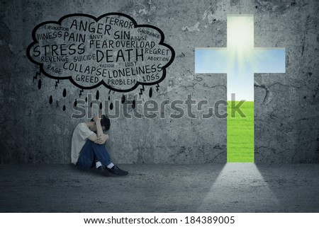 Young man desperate sitting on the floor with cross symbol next to him - stock photo