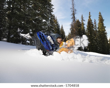 Young man digging out snowmobile submerged in the snow.