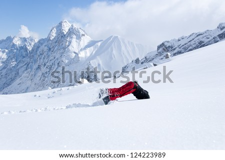 Young man diving head first into untouched powder snow with panorama of mountains in background - stock photo