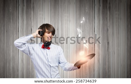 Young man dj wearing headphones and holding plate - stock photo