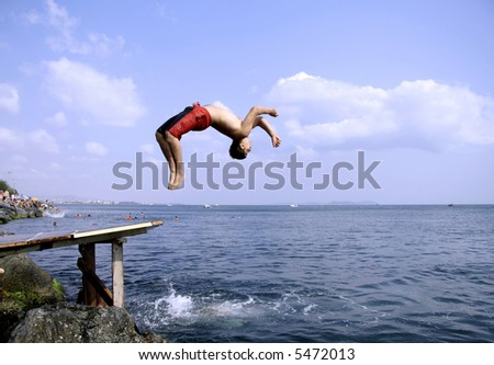 young man doing a back flip into sea, istanbul, turkey - stock photo