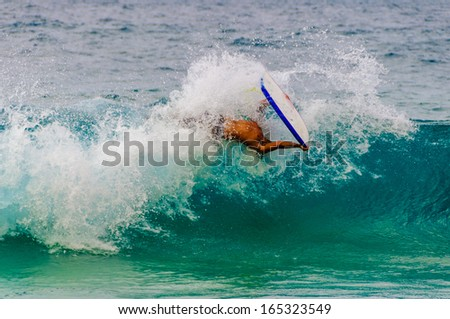 Young man doing a barrel roll while boogie boarding on Maui, Hawaii, USA