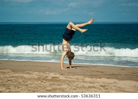 Young man doing a relaxed handstand at the beach near Pacific ocean - stock photo