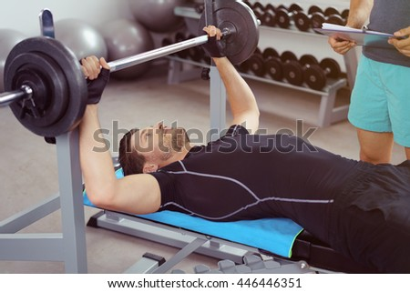 Young man doing bodybuilding exercises in a gym lifting a barbell weight on a bench with a gym instructor standing by - stock photo