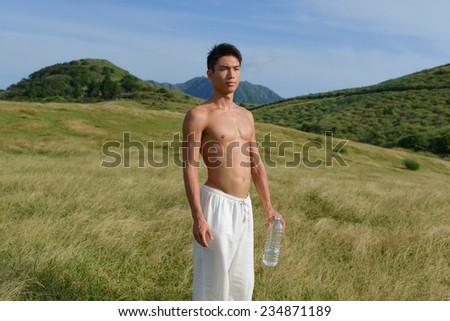young man doing exercise holding a bottle of clear liquid - outdoors