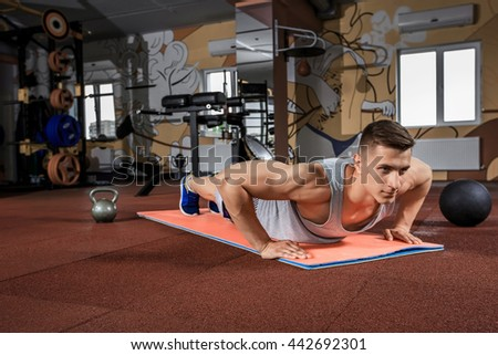 Young man doing exercises in the gym