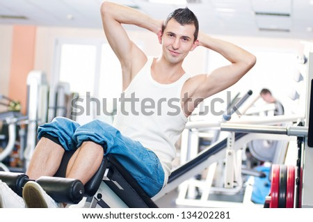Young man doing exercises with sport equipment at gym club - stock photo